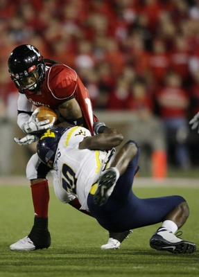 CINCINNATI - NOVEMBER 13: Isaiah Pead #23 of the Cincinnati Bearcats is tackled by J.T. Thomas #30 of the West Virginia Mountaineers during the third quarter of the game at Nippert Stadium on November 13, 2009 in Cincinnati, Ohio.  (Photo by Andy Lyons/Ge