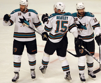 CHICAGO - MAY 21:  (L-R) Joe Thornton #19, Dany Heatley #15, Patrick Marleau #12 and Dan Boyle #12 of the San Jose Sharks react after the second period goal by Marleau while taking on the Chicago Blackhawks in Game Three of the Western Conference Finals d