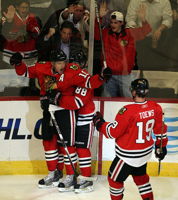 CHICAGO - OCTOBER 27: Patrick Sharp #10 of the Chicago Blackhawks get a hug from teammate Patrick Kane #88 as he celebrates a 3rd period goal against the Los Angeles Kings while Jonathan Toews skates to join them at the United Center on October 27, 2010 i