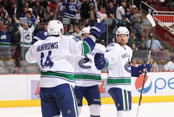 GLENDALE, AZ - FEBRUARY 02:  Alex Burrows #14 of the Vancouver Canucks is celebrates with teammates Daniel Sedin #22 and Henrik Sedin #33 after Burrows scored a first period goal against the Phoenix Coyotes during the NHL game at Jobing.com Arena on Febru