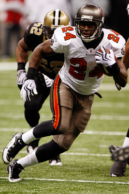 NEW ORLEANS - DECEMBER 27:  Cadillac Williams #24 of the Tampa Bay Buccaneers runs past Jonathan Casillas #52  of the New Orleans Saints at the Louisiana Superdome on December 27, 2009 in New Orleans, Louisiana.  (Photo by Chris Graythen/Getty Images)