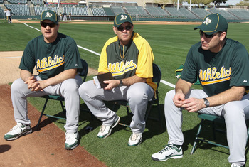PHOENIX, AZ - FEBRUARY 16:  (L-R) Manager Bob Geren, pitching coach Ron Romanick and bench coach Joel Skinner of the Oakland Athletics talk with players during a MLB spring training practice at Phoenix Municipal Stadium on February 16, 2011 in Phoenix, Ar