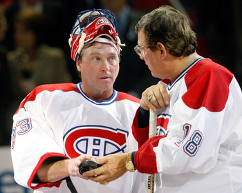 MONTREAL- DECEMBER 4:  Former Montreal Canadiens Serge Savard hands a puck to Patrick Roy during the Centennial Celebration ceremonies prior to the NHL game between the Montreal Canadiens and Boston Bruins on December 4, 2009 at the Bell Centre in Montrea