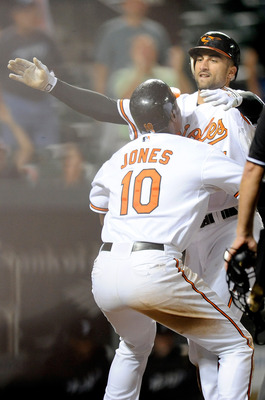 BALTIMORE - SEPTEMBER 13:  Nick Markakis #21 of the Baltimore Orioles celebrates with Adam Jones #10 after scoring the winning run in the eleventh inning against the Toronto Blue Jays at Camden Yards on September 13, 2010 in Baltimore, Maryland. The Oriol