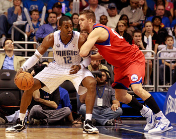 ORLANDO, FL - DECEMBER 18:  Spencer Hawes #00 of the Philadelphia 76ers guards Dwight Hoawrd #12 of the Orlando Magic during the game at Amway Arena on December 18, 2010 in Orlando, Florida.  NOTE TO USER: User expressly acknowledges and agrees that, by d