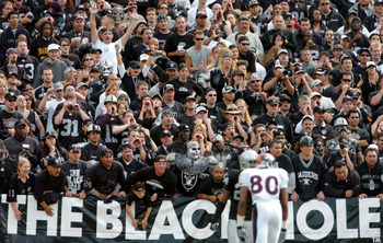 OAKLAND, CA - OCTOBER 17:  Fans in the black hole cheer as Rod Smith #80 of the Denver Broncos and Charles Woodson #24 of the Oakland Raiders line up at scrimmage at the Network Associates Coliseum on October 17, 2004 in Oakland, California.  (Photo by Tr