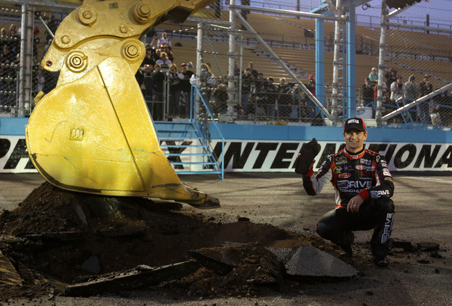 AVONDALE, AZ - FEBRUARY 27:  Jeff Gordon, driver of the #24 Drive to End Hunger Chevrolet, poses with a piece of the track after using an excavator to tear up the race track, following his win in the NASCAR Sprint Cup Series Subway Fresh Fit 500 at Phoeni