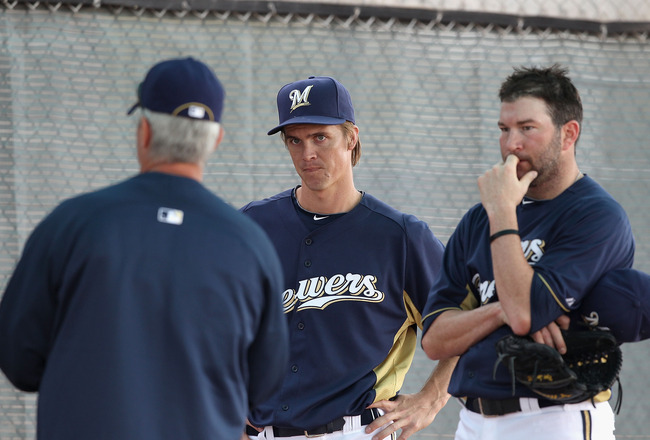 PHOENIX, AZ - FEBRUARY 18:  Pitchers Zack Greinke #13 (C) and Shaun Marcum #18 (R) of the Milwaukee Brewers listen to pitching coach Rick Kranitz (L) during a MLB spring training practice at Maryvale Baseball Park on February 18, 2011 in Phoenix, Arizona.