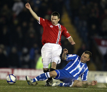 BURY, ENGLAND - DECEMBER 08:  Matthew Wolfenden of FC United is challenged by Gary Hart of Brighton  during the FA Cup sponsored by E.ON 2nd Round Replay between FC United of Manchester and Brighton &amp; Hove Albion at Gigg Lane on December 8, 2010 in Bury,
