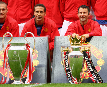 MANCHESTER, UNITED KINGDOM - AUGUST 06:  Rio Ferdinand of Manchester United and team mate Ryan Giggs (R) pose with the Premier League and Champions League trophies prior to the Pre Season Friendly match between Manchester United and Juventus at Old Traffo