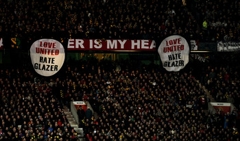 MANCHESTER, ENGLAND - MARCH 10: Manchester United fans reveal anti Glazer banners during the UEFA Champions League First Knockout Round, second leg match between Manchester United and AC Milan at Old Trafford on March 10, 2010 in Manchester, England. (Pho