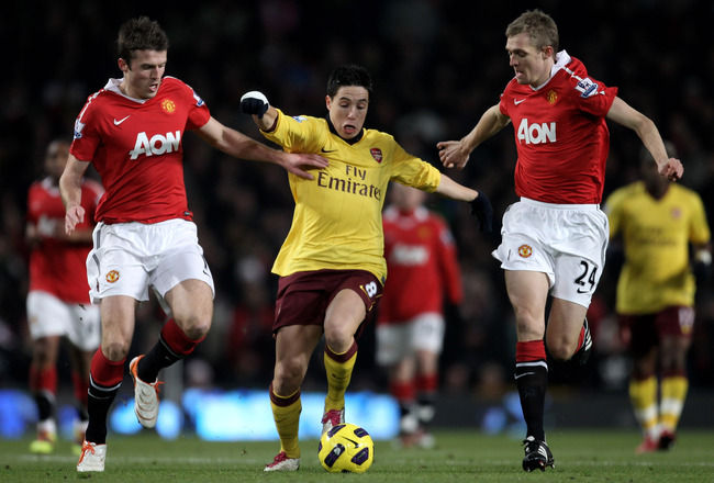 MANCHESTER, ENGLAND - DECEMBER 13:  Samir Nasri of Arsenal competes with Darren Fletcher (R) and Michael Carrick of Manchester United during the Barclays Premier League match between Manchester United and Arsenal at Old Trafford on December 13, 2010 in Ma