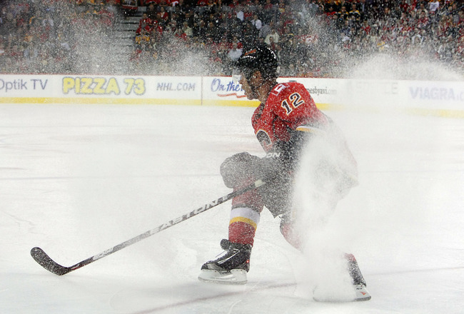 CALGARY,CANADA - FEBRUARY 22:  Jarome Iginla #12 of the Calgary Flames stops as ice sprays up while facing the Boston Bruins during their NHL game at Scotiabank Saddledome, February 22,2011 in Calgary, Alberta, Canada.  (Photo By Dave Sandford/Getty Image