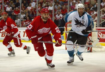 DETROIT - APRIL 28:  Mathieu Schneider #23 of the Detroit Red Wings and Joe Thornton #19 of the San Jose Sharks pursue the play during Game 2 of the 2007 NHL Western Conference Semifinals at Joe Louis Arena on April 28, 2007 in Detroit, Michigan. (Photo B