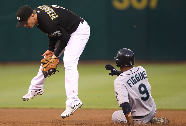 OAKLAND, CA - SEPTEMBER 8:  Chone Figgins #9 of the Seattle Mariners steals second base as Cliff Pennington #2 of  the Oakland Athletics fields the throw in the first inning during a Major League Baseball game at the Oakland-Alameda County Coliseum on Sep