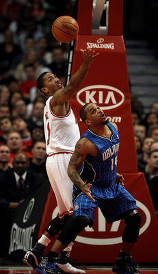 CHICAGO, IL - JANUARY 28: Derrick Rose #1 of the Chicago Bulls reaches for the ball over Jameer Nelson #14 of the Orlando Magic at the United Center on January 28, 2011 in Chicago, Illinois. NOTE TO USER: User expressly acknowledges and agrees that, by do