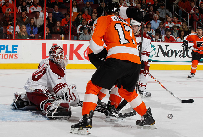 PHILADELPHIA - FEBRUARY 22:  Goaltender IIya Bryzgalov #30 of the Phoenix Coyotes makes a pad save as Jeff Carter #17 of the Philadelphia Flyers looks for the rebound on February 22, 2011 at the Wells Fargo Center in Philadelphia, Pennsylvania. Coyotes de