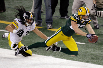 ARLINGTON, TX - FEBRUARY 06:  Jordy Nelson #87 of the Green Bay Packers catches a pass and runs 38 yards as Troy Polamalu #43 of the Pittsburgh Steelers knocks him out of bounds during Super Bowl XLV at Cowboys Stadium on February 6, 2011 in Arlington, Te