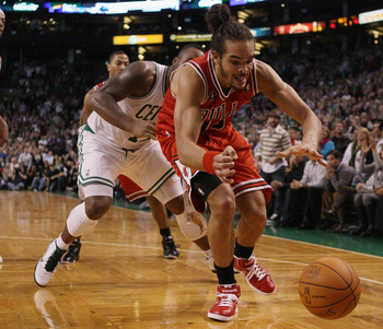 BOSTON - NOVEMBER 05:  Joakim Noah #13 of the Chicago Bulls and Glen Davis #11 of the Boston Celtics chase after a loose ball on November 5, 2010 at the TD Garden in Boston, Massachusetts. The Celtics defeated the Bulls 110-105 in overtime. NOTE TO USER: