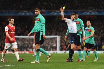 LONDON, ENGLAND - FEBRUARY 16: Referee Nicola Rizzoli shows the yellow card to Gerard Pique of Barcelona during the UEFA Champions League round of 16 first leg match between Arsenal and Barcelona at the Emirates Stadium on February 16, 2011 in London, Eng