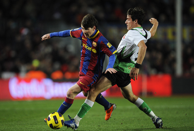 BARCELONA, SPAIN - JANUARY 22:  Lionel Messi of Barcelona (R) duels for the ball against Christian Fernandez of Racing Santander during the La Liga match between Barcelona and Racing Santander at Camp Nou on January 22, 2011 in Barcelona, Spain.  Barcelon