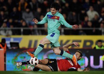 MALLORCA, SPAIN - FEBRUARY 26:  Lionel Messi of FC Barcelona duels for the ball against Ruben Gonzalez of Mallorca during the La Liga match between Mallorca and Barcelona at Iberstar Stadium on February 26, 2011 in Mallorca, Spain. Barcelona won 3-0.  (Ph