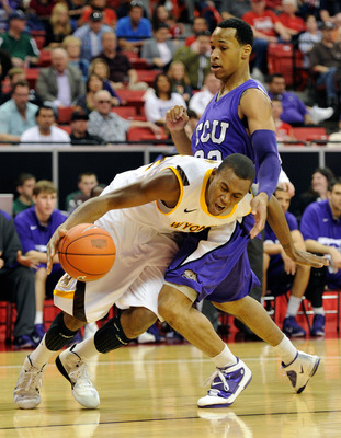 LAS VEGAS, NV - MARCH 09:  Garlon Green #33 of the Texas Christian University Horned Frogs fouls Amath M'Baye #22 of the Wyoming Cowboys during the first round of the Conoco Mountain West Conference Basketball tournament at the Thomas & Mack Center March