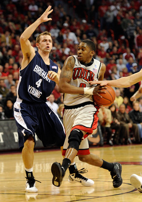 LAS VEGAS, NV - JANUARY 05:  Oscar Bellfield #0 of the UNLV Rebels has the ball knocked away from behind as he drives against Jackson Emery #4 of the Brigham Young University Cougars during their game at the Thomas & Mack Center January 5, 2011 in Las Veg