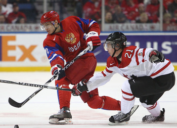 BUFFALO, NY - DECEMBER 26: Defenseman Nikita Zaitsev #2 of Russia dumps the puck in as forward Cody Eakin #21 of Canada tries to block the puck during the 2011 IIHF World U20 Championship Group B game between Canada and Russia on December 26, 2010 at HSBC