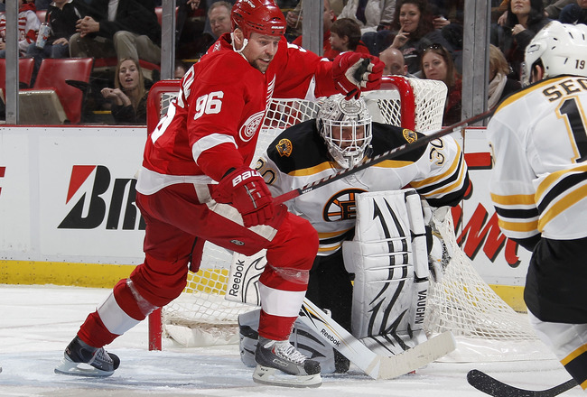 DETROIT, MI - FEBRUARY 13:  Tomas Holmstrom #96 of the Detroit Red Wings tries to get to the puck in front of Tim Thomas #30 of the Boston Bruins on February 13, 2011 at Joe Lewis Arena in Detroit, Michigan.  (Photo by Gregory Shamus/Getty Images)