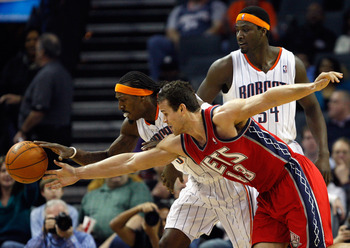 CHARLOTTE, NC - FEBRUARY 11:  Kris Humphries #43 of the New Jersey Nets battles for a loose ball with teammates Kwame Brown #54 and Gerald Wallace #3 of the Charlotte Bobcats during their game at Time Warner Cable Arena on February 11, 2011 in Charlotte,