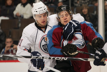 DENVER, CO - FEBRUARY 23:  John-Michael Liles #4 of the Colorado Avalanche is restrained by Magnsu Paajarvi #91 of the Edmonton Oilers at the Pepsi Center on February 23, 2011 in Denver, Colorado. Elliott collected the loss as the Oilers defeated the Avla