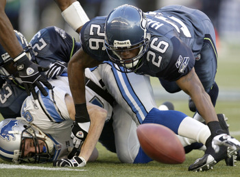 SEATTLE - NOVEMBER 16:  Wide Receiver Bill Schroeder #84 of the Detroit Lions fumbles against Ken Hamlin #26 of the Seattle Seahawks on November 16, 2003 at Seahawks Stadium in Seattle, Washington. The Lions recovered the ball.  (Photo by Otto Greule Jr/G