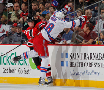 NEWARK, NJ - FEBRUARY 18:  Nick Palmieri #32 of the New Jersey Devils checks Marc Staal #18 of the New York Rangers during the second period of an NHL hockey game at the Prudential Center on February 18, 2011 in Newark, New Jersey.  (Photo by Paul Bereswi
