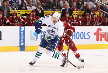 GLENDALE, AZ - FEBRUARY 02:  Daniel Sedin #22 of the Vancouver Canucks shoots the puck under pressure from Kyle Turris #91 of the Phoenix Coyotes during the NHL game at Jobing.com Arena on February 2, 2011 in Glendale, Arizona.  (Photo by Christian Peters