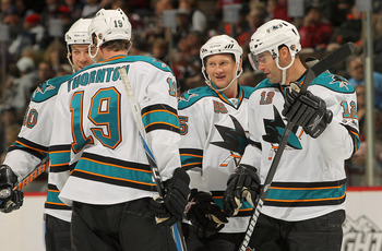 DENVER - NOVEMBER 17:  Mike Moore #55 (2nd R) of the San Jose Sharks celebrates his second period goal against the Colorado Avalanche with teammates Patrick Marleau #12, Joe Thornton #19 and Kent Huskins #40 at the Pepsi Center on November 17, 2010 in Den
