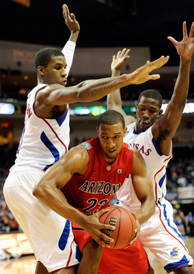 LAS VEGAS - NOVEMBER 27:  Derrick Williams #23 of the Arizona Wildcats drives between Thomas Robinson (L) #0 and Mario Little #23 of the Kansas Jayhawks during the championship game of the Las Vegas Invitational at The Orleans Arena November 27, 2010 in L