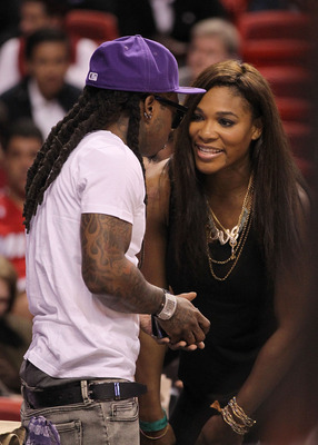 MIAMI, FL - DECEMBER 01:  Tennis star Serena Williams talks with Rapper Lil' Wayne during a game between the Miami Heat  and the Detroit Pistons at American Airlines Arena on December 1, 2010 in Miami, Florida. NOTE TO USER: User expressly acknowledges an