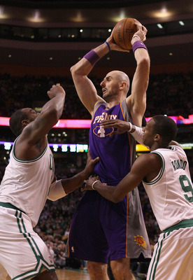 BOSTON, MA - MARCH 02:  Marcin Gortat #4 of the Phoenix Suns looks to pass as Glen Davis and Rajon Rondo #9 of the Boston Celtics defend on March 2, 2011 at the TD Garden in Boston, Massachusetts.  The Celtics defeated the Suns 115-103. NOTE TO USER: User