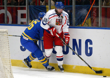 STOCKHOLM, SWEDEN - SEPTEMBER 7:  Jiri Dopita #30 of the Czech Republic moves the puck along the boards against Samuel Pahlsson #26 of Sweden during a quarterfinal game in the World Cup of Hockey tournament at the Globe Arena on September 7, 2004 in Stock