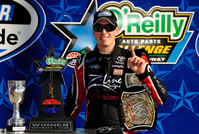 FORT WORTH, TX - NOVEMBER 07:  Kyle Busch, driver of the #18 Z-Line Designs/WWE Smackdown Toyota,  poses on victory lane with the trophy and a replica of the WWE world championship belt after winning the NASCAR Nationwide Series O'Reilly Challenge at Texa