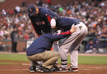 SAN FRANCISCO - JUNE 25:  Dustin Pedroia #15 of the Boston Red Sox looks on as manager Terry Francona and a trainer examine his leg after being struck by a foul ball against the San Francisco Giants in the third inning during an MLB game at AT&T Park on J