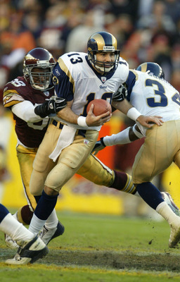 LANDOVER, MD - NOVEMBER 24:  Quarterback Kurt Warner #13 of the St. Louis Rams eludes the grasp of #58 Antonio Pierce #58 of the Washington Redskins in the 4th quarter on November 24, 2002 at FedEx Field in Landover Maryland.  (Photo by Al Bello/Getty Ima