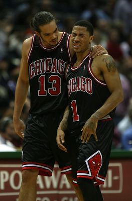MILWAUKEE - NOVEMBER 30: Joakim Noah #13 of the Chicago Bulls consoles teammate Derrick Rose #1 during a time-out after Rose was fouled during a game against the Milwaukee Bucks at the Bradley Center on November 30, 2009 in Milwaukee, Wisconsin. The Bucks