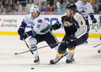 NASHVILLE, TN - FEBRUARY 17:  Tanner Glass #15 of the Vancouver Canucks skates against Cody Franson #4 of the Nashville Predators on February 17, 2011 at the Bridgestone Arena in Nashville, Tennessee.  (Photo by Frederick Breedon/Getty Images)