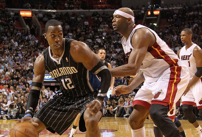 MIAMI, FL - MARCH 03:  Dwight Howard #12 of the Orlando Magic drives against Eric Dampier #25 of the Miami Heat during a game at American Airlines Arena on March 3, 2011 in Miami, Florida. NOTE TO USER: User expressly acknowledges and agrees that, by down