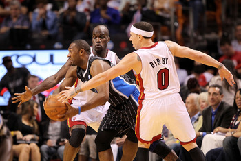 MIAMI, FL - MARCH 03:  Gilbert Arenas #1 of the Orlando Magic passes around Mike Bibby #0 and Joel Anthony #50 of the Miami Heat during a game at American Airlines Arena on March 3, 2011 in Miami, Florida. NOTE TO USER: User expressly acknowledges and agr