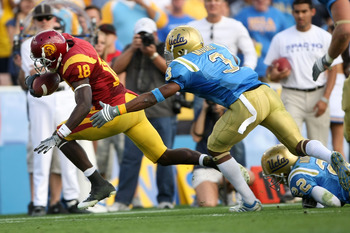 PASADENA, CA - DECEMBER 06:  Damian Williams #18 of the USC Trojans runs into the end zone for a touchdown past Michael Norris #22 and Rahim Moore #3 of the UCLA Bruins in the first half of the game on December 6, 2008 at the Rose Bowl in Pasadena, Califo