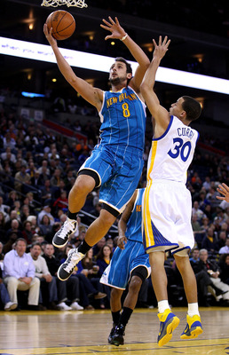 OAKLAND, CA - JANUARY 26:  Marco Belinelli #8 of the New Orleans Hornets drives on Stephen Curry #30 of the Golden State Warriors at Oracle Arena on January 26, 2011 in Oakland, California.  NOTE TO USER: User expressly acknowledges and agrees that, by do
