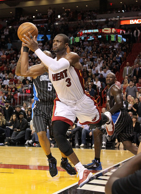 MIAMI, FL - MARCH 03:  Dwyane Wade #3 of the Miami Heat passes around Quentin Richardson #5 of the Orlando Magic during a game at American Airlines Arena on March 3, 2011 in Miami, Florida. NOTE TO USER: User expressly acknowledges and agrees that, by dow